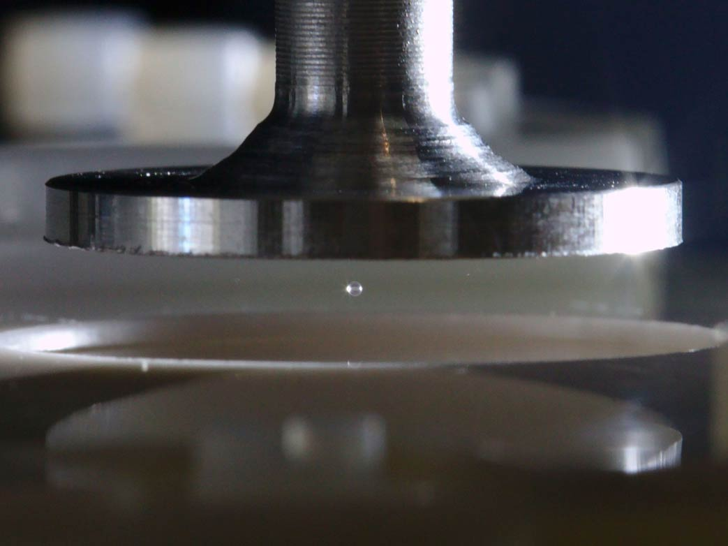 Ultrasound waves emitted by vibrating a metal disk levitate a glass sphere a fraction of a millimeter big. Once the sound is stopped, the sphere falls down on the surface underneath allowing scientists to study the exchange of electric charges. © IST Austria
