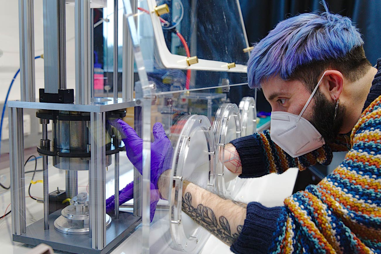 While controlling the humidity in the experimental chamber, PhD student Juan Carlos Sobarzo measures the charge that builds up when two identical surfaces touch. © Nadine Poncioni, IST Austria
